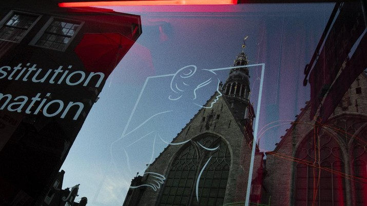 Oude Kerk, or Old Church, is reflected in the window of the PIC, Prostitution Information Center, as sex workers welcomed clients again in the Red Light District in Amsterdam, Netherlands, Wednesday, July 1, 2020. It wasn't quite business as usual as the capital's Red Light District emerged from coronavirus lockdown, but it was as close as it has been since the pandemic slammed the brakes on the world's oldest profession. (AP Photo/Peter Dejong)