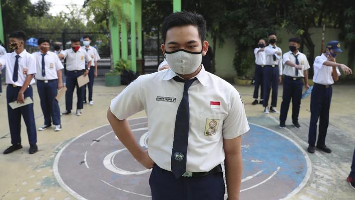 Siswa menggunakan masker dihari pertama masuk sekolah negeri di Bekasi. AP/Achmad Ibrahim
