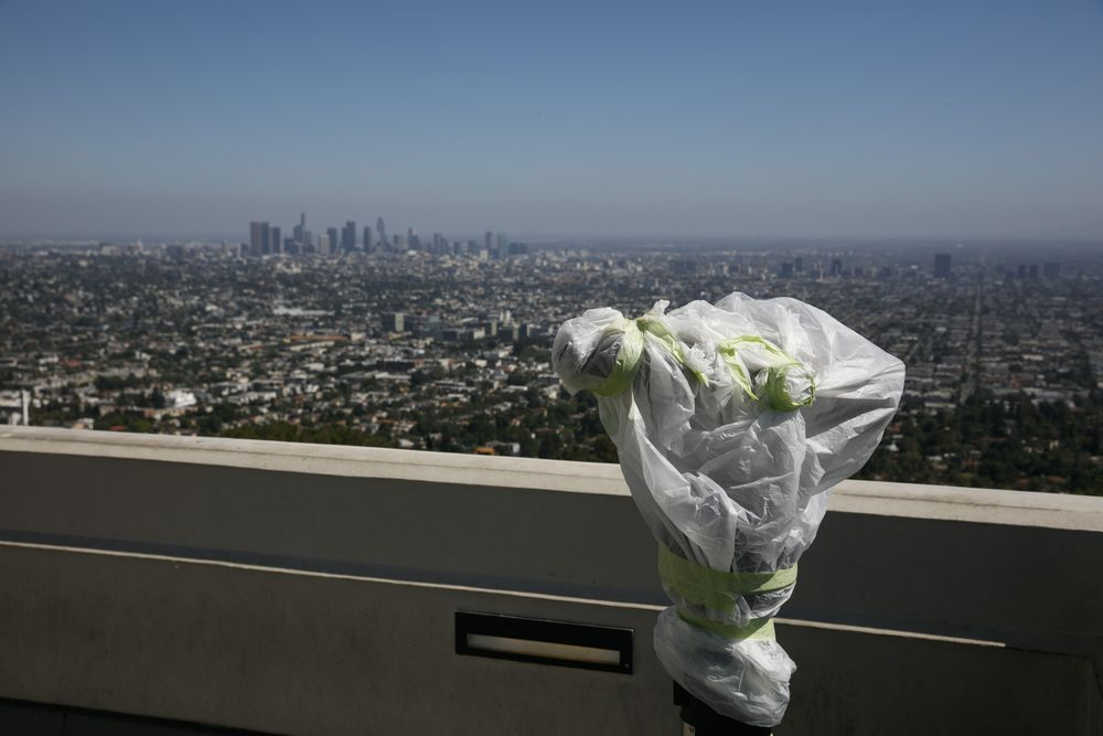 A telescope is seen wrapped in plastic to prevent the spread of COVID-19 at the Griffith Observatory overlooking downtown Los Angeles, Wednesday, July 15, 2020. Coronavirus cases have surged to record levels in the Los Angeles area, putting the nation's largest county in