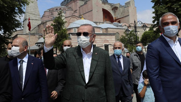 Turkey's President Recep Tayyip Erdogan, center, salutes supporters as he visits the Byzantine-era Hagia Sophia, in the background, one of Istanbul's main tourist attractions in the historic Sultanahmet district of Istanbul, Sunday, July 19, 2020, days after he formally reconverted Hagia Sophia into a mosque and declared it open for Muslim worship, after a high court annulled a 1934 decision that had made the religious landmark a museum.(Turkish Presidency via AP, Pool)