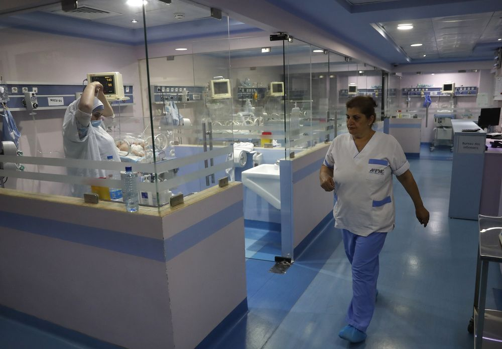 Nurses work at the neonatal intensive care unit, at Family Medical Center, a private hospital facing financial difficulties, in Majdalaiya village, north Lebanon, Thursday, July 16, 2020. Just as Lebanon faces a surge in coronavirus cases, hospitals are cracking under the country's financial crisis. They are struggling to pay staff, keep equipment running or even stay open amid shortages in key supplies like anesthesia and sutures. The health sector has long been one of the best in the Middle East, with its private hospitals drawing patients from around the region. But with dollars in short supply and the state unable to pay insurance bills, hospitals are having to turn away patients and close wards to cut costs. Public facilities, on the front line of the coronavirus fight, are too underfunded and understaffed to fill the gap. (AP Photo/Hussein Malla)