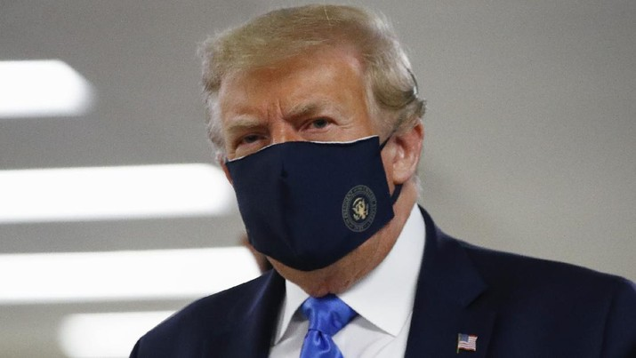 """FILE - In this July 11, 2020, file photo President Donald Trump wears a face mask as he walks down a hallway during a visit to Walter Reed National Military Medical Center in Bethesda, Md. On Tuesday, July 21, Trump professed a newfound respect for the protective face masks he has seldom worn. """"Whether you like the mask or not, they have an impact,"""