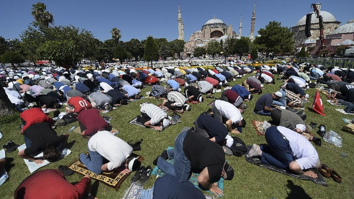 Muslims pray during Friday prayers at the historic Sultanahmet district of Istanbul, near the Byzantine-era Hagia Sophia, background, Friday, July 24, 2020. Thousands of Muslim faithful surrounded Istanbul's landmark monument Friday to take part in the first prayers in 86 years at the structure that was once Christendom's most significant cathedral and the
