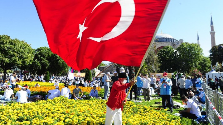 A man waves a Turkish flag outside the Byzantine-era Hagia Sophia, in the historic Sultanahmet district of Istanbul, Friday, July 24, 2020. Hundreds of Muslim faithful were making their way to Istanbul's landmark monument Friday to take part in the first prayers in 86 years at the structure that was once Christendom's most significant cathedral and the