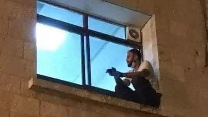 Seorang pria naik ke jendela rumah sakit saat ibunya dirawat akibat Covid-19. (Tangkapan Layar Twitter @mhdksafa)