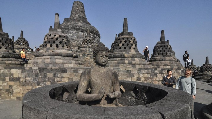 In this Monday, Aug. 12, 2019, photo, tourists inspect a Buddha statue at Borobudur Temple in Magelang, Central Java, Indonesia. The Indonesian city of Yogyakarta and its hinterland are packed with tourist attractions, including Buddhist and Hindu temples of World Heritage. Yet many tourists still bypass the congested city and head to the relaxing beaches of Bali. Recently re-elected President Joko Widodo wants to change this dynamic by pushing ahead with creating