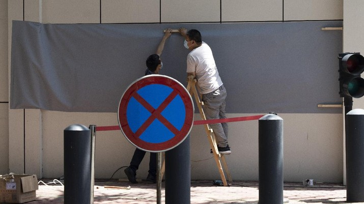 Workers prepare to cover up the areas where the signage used to show the location as United States Consulate in Chengdu in southwest China's Sichuan province on Monday, July 27, 2020. Chinese authorities took control of the former U.S. consulate in the southwestern Chinese city of Chengdu on Monday after it was ordered closed in retaliation for a U.S. order to vacate the Chinese Consulate in Houston. (AP Photo/Ng Han Guan)