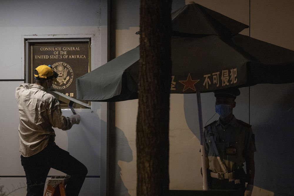 A worker tries to remove the plaque from the United States Consulate near a Chinese paramilitary policeman on guard in Chengdu in southwest China's Sichuan province on Sunday, July 26, 2020. The ongoing sharp deterioration in U.S.-China ties poses risks to both countries and the rest of the world. In the latest escalation, a U.S. consulate in Chengdu in southwestern China shuttered Monday, ordered by China to close in retaliation for the U.S. shutting down its consulate in Houston last week. (AP Photo/Ng Han Guan)