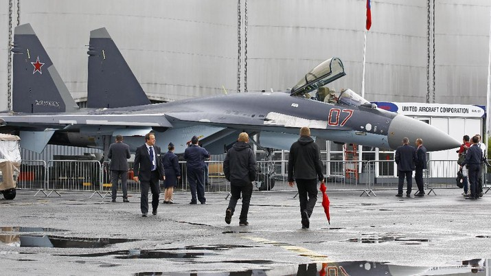 Visitors look at a Sukhoi SU-35 made by United Aircraft Corporation, displayed at the 50th Paris Air Show at Le Bourget airport, north of Paris, Thursday June 20, 2013. (AP Photo/Remy de la Mauviniere)