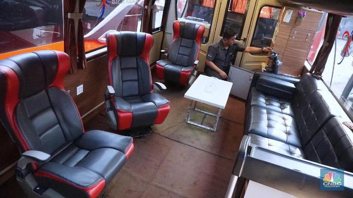 Petugas merapihkan deretan bus di Pool Bus Pariwisata Kawasan Tanjung Barat, Jakarta Selatan, Selasa (28/7/2020). Masih diberlakukannya Pembatasan Sosial Bersekala Besar (PSBB) dan penutupan tempat rekreasi akibat Covid-19, berimbas pada jasa transportasi pariwisata.   Penutupan obyek wisata dan imbauan untuk tidak ke tempat keramaian demi mencegah penyebaran corona (covid-19) membuat Perusahaan Otobus (PO) pariwisata mengandangkan armadanya. Padahal, momen sebelum datangnya Ramadhan merupakan waktunya para pemilik perusahaan otobus panen rezeki. PO terpaksa mengandangkan armadanya karena berbagai acara keluar kota dibatalkan. Permasalahan tak berhenti di situ saja, bayang-bayang setoran cicilan ke perusahaan leasing juga menghantui para pemilik PO ini.   Fajar, Head Marketing bus Manhattan, pada CNBC Indonesia, menjelaskan para usaha bus sejak pandemi ini terpuruk. Apalagi, menurut Fajar, pesanan bus biasanya sudah ramai lagi pada H-7 Lebaran kemarin.  Dengan kondisi seperti ini, banyak bus yang dikandangkan, akibatnya membuat pemasukan tidak ada.
