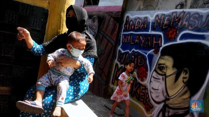 Warga mengenakan masker di Kawasan Kampung Rawa Pasung RW 022, Kelurahan Kota Baru, Kecamatan Bekasi Barat, Kota Bekasi, Jawa Barat, Selasa (28/7/2020).  Lokasi yang berbatasan dengan Jakarta Timur ini , kampung rawa pasung bekasi ini dikenal sebagai wilayah zona hijau sejak awal pandemi Maret lalu.  Beragam mural berisi pesan kepatuhan terhadap protokol kesehatan menghiasi gang sempit di kawasan hunian padat tersebut.  Warga sukarela memberikan paket sembako gratis bagi warga lain yang membutuhkan dan menyediakan ruang isolasi mandiri untuk yang terkena Covid-19.  Pak Soleh selaku ketua RW mengklaim bahwa kampung tersebut 0 positif Corona dan masuk zona hijau.