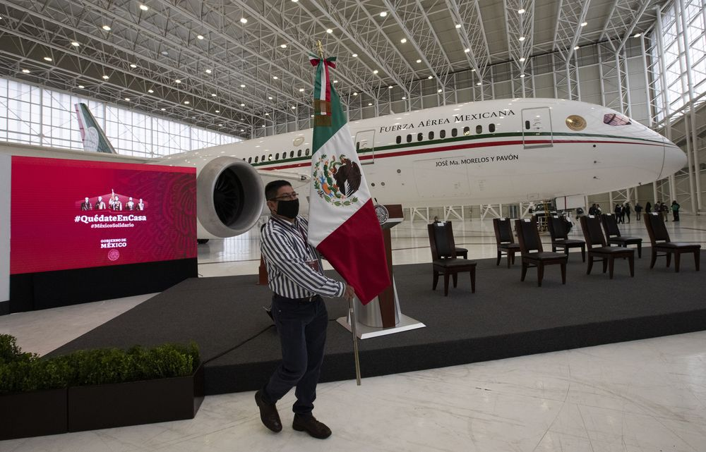 A soldier stands guard inside the former Mexican presidential plane during a media tour following the daily, morning press conference of Mexican President Andres Manuel Lopez Obrador at Benito Juarez International Airport in Mexico City, Monday, July 27, 2020. The president, who only flies commercial as one measure in his austerity government, has been trying to sell the plane since he took office. (AP Photo/Marco Ugarte)