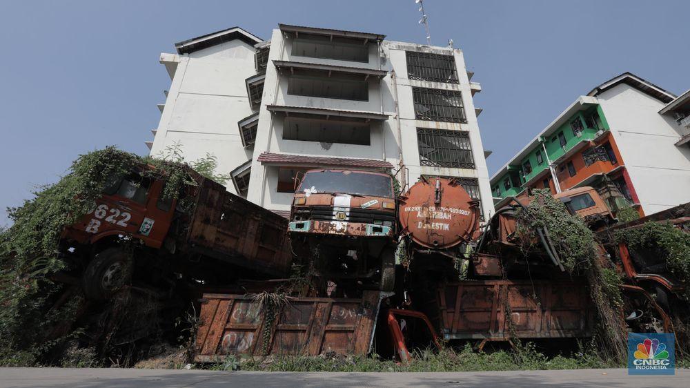 Kendaraan armada tua menumpuk dibelakang rusun Cengkareng, Jakarta Barat, Rabu (29/7/20). (CNBC Indonesia/Tri Susilo)   Lahan rusun belakang Cengkareng, Jakarta Barat menjadi tempat penampungan kendaraan pengangkut sampah tua yang tak lagi dipakai.  Berdasarkan pantauan CNBC Indonesia pada Rabu (29/7/20), belakang halaman rusun tersebut dipenuhi truk sampah yang terlihat tua. Beberapa bagiannya berkarat dan keropos. Truk sampah itu ditumpuk begitu saja.  Dulunya mobil-mobil tak terpakai tersebut diletakkan berbaris di halaman belakang rusun Cengkareng Hingga akhirnya, pihak Sudin Lingkungan Hidup Jakarta Barat bersiasat untuk meletakkannya secara bertumpuk.     Ada kurang lebih 30 kendaraan kendaraan yang terparkir di halaman rusun tersebut . Ada pula mobil tangki air yang diparkir di atas tumpukan.     Kondisi kendaraan-kendaraan tersebut berbeda-beda. Ada yang sudah tak memiliki ban, kaca pecah, bodi penyok, jok mobil reyot dan lainnya.    Dilokasi pemumpukan kendaraan dimanfaatkan sebagian warga mencari rumput untuk pakan hewan mereka.  Kondisi ini dimanfaatkan anak anak yang tidur didalam tumpukan kendaraan.   kendaraan tersebut sudah tidak layak pakai. Kendaraan itu ada sejak 1997 dan kini rusak. (CNBC Indonesia/ Tri Susilo)
