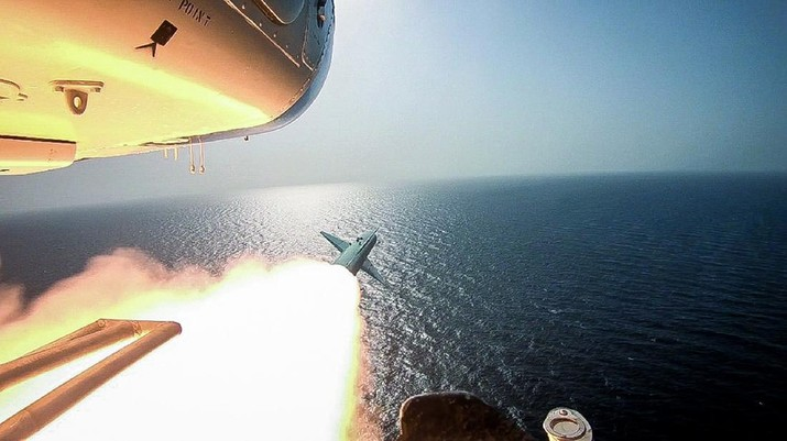 In this photo released Tuesday, July 28, 2020, by Sepahnews, Revolutionary Guard's helicopter fires a missile during an exercise. Iran's paramilitary Revolutionary Guard fired a missile from a helicopter targeting a replica aircraft carrier in the strategic Strait of Hormuz, state television reported on Tuesday, an exercise aimed at threatening the U.S. amid tensions between Tehran and Washington. (Sepahnews via AP)