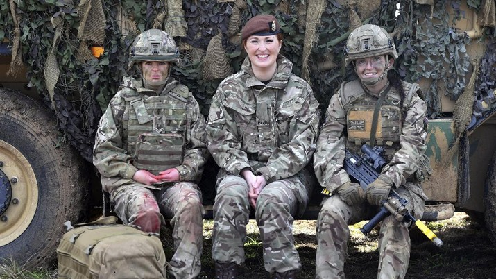 From left, Royal Army Medical Cops medic Corporal Vicky Helsby, 29, from Runcorn, Royal Wessex Yeomanry Tank Gunner reservist Lance Corporal Kat Dixon, 28, from Swindon and Royal Army Veterinary Corps Dog Handler Private Beth Johnson, 19, from Bridgwater during a Land Combat demonstration featuring women in command posts at Copehill Down Village on Salisbury Plain, Wiltshire. Women can now serve in all roles in Britain's military, including front-line combat units and the special forces. Defense Secretary Gavin Williamson announced the change Thursday, saying