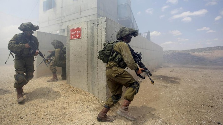 Israeli soldiers run during an exercise which simulates warfare in the Gaza Strip, at an army base in the south of Israel, Monday, July 14, 2014. Israel began its campaign against militants in the Hamas-controlled Gaza last Tuesday, saying it was responding to heavy rocket fire from the densely populated territory. The military says it has launched more than 1,300 airstrikes since then, while Palestinian militants have launched nearly 1,000 rockets at Israel. (AP Photo/Tsafrir Abayov)