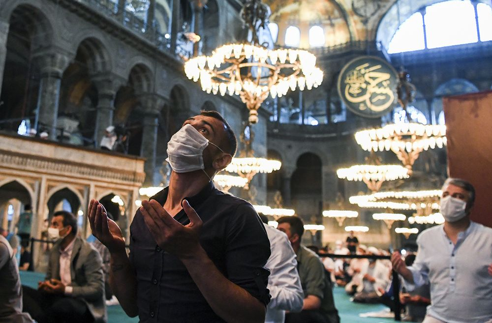 "Muslims, wearing protective masks as a precaution against infection from coronavirus, gather for the Eid al-Adha prayer inside the Byzantine-era Hagia Sophia, recently converted back to a mosque, in the historic Sultanahmet district of Istanbul, Friday, July 31, 2020. Small groups of pilgrims performed one of the final rites of the Islamic hajj on Friday as Muslims worldwide marked the start of the Eid al-Adha holiday amid a global pandemic that has impacted nearly every aspect of this year's pilgrimage and celebrations. The last days of hajj coincide with the four-day Eid al-Adha, or ""Feast of Sacrifice,"" in which Muslims slaughter livestock and distribute the meat to the poor.  (Pool via AP)"