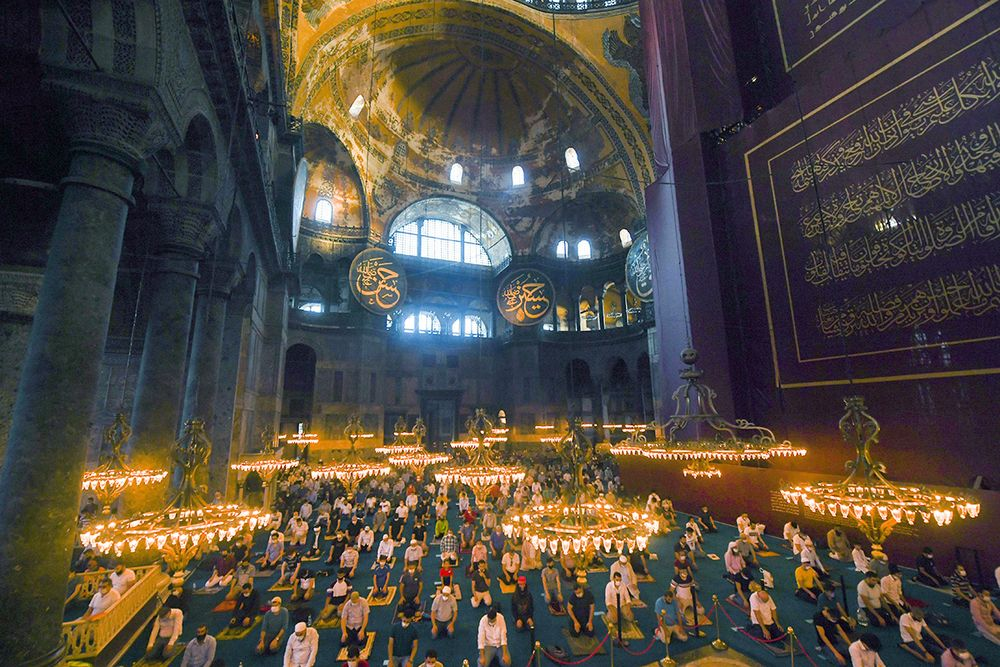 "Muslims, wearing protective masks as a precaution against infection from coronavirus gather for the Eid al-Adha prayer inside the Byzantine-era Hagia Sophia, recently converted back to a mosque, in the historic Sultanahmet district of Istanbul, Friday, July 31, 2020. Small groups of pilgrims performed one of the final rites of the Islamic hajj on Friday as Muslims worldwide marked the start of the Eid al-Adha holiday amid a global pandemic that has impacted nearly every aspect of this year's pilgrimage and celebrations. The last days of hajj coincide with the four-day Eid al-Adha, or ""Feast of Sacrifice,"" in which Muslims slaughter livestock and distribute the meat to the poor.  (Pool via AP)"