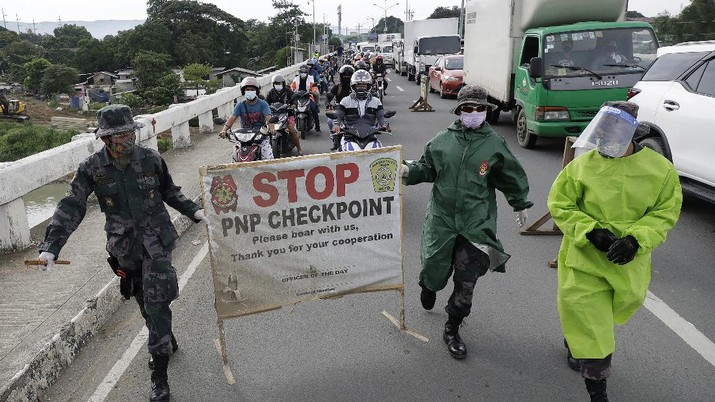 Police officers wearing protective gear carry a checkpoint sign on a roadway Tuesday, Aug. 4, 2020, outside Manila, Philippines, as the capital is placed on another lockdown in the hopes of controlling the surge of coronavirus cases. Commuter trains, buses and other public vehicles stayed off the main roads of the Philippine capital Tuesday and police were again staffing checkpoints to restrict public travel. (AP Photo/Aaron Favila)