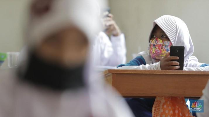 Belasan siswa melakukan kegiatan belajar mengajar sistem online di ruang aula kelurahan Jatirahayu, Bekasi, Jawa Barat. (CNBC Indonesia/Muhammad Sabki)