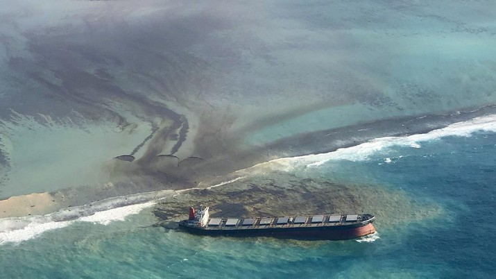 This photo taken and provided by Eric Villars shows oil leaking from the MV Wakashio, a bulk carrier ship that recently ran aground off the southeast coast of Mauritius, Friday, Aug. 7, 2020. Anxious residents of the Indian Ocean island nation of Mauritius are stuffing fabric sacks with sugar cane leaves to create makeshift oil spill barriers as tons of fuel leak from a grounded ship. The government has declared an environmental emergency and France says it is sending help from its nearby Reunion island. (Eric Villars via AP)