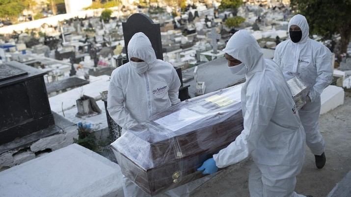 Cemetery workers in full protective gear carry the coffin containing the remains of Maria Pereira, 72, who died from the new coronavirus, at the municipal cemetery in Nova Iguacu, Brazil, Friday, Aug. 7, 2020. COVID-19 deaths in Brazil are rapidly approaching 100,000. (AP Photo/Silvia Izquierdo)