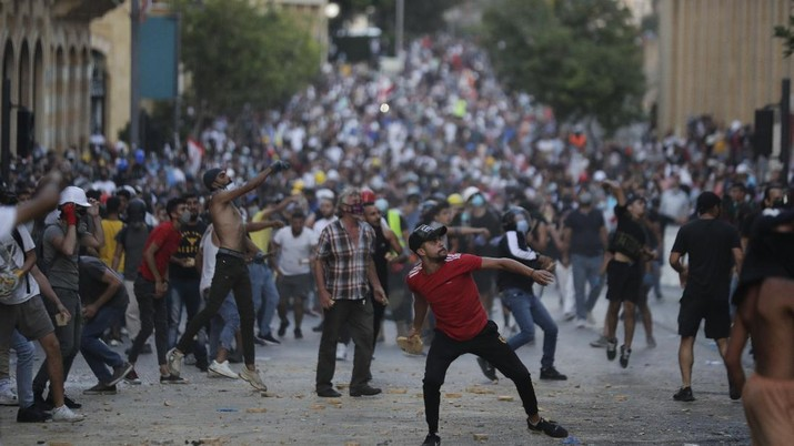 People throw stones during anti-government protest following Tuesday's massive explosion which devastated Beirut, Lebanon, Sunday, Aug. 9. 2020. (AP Photo/Hassan Ammar)