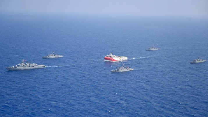 In this photo provided by the Turkish Defense Ministry, Turkey's research vessel, Oruc Reis, in red and white, is surrounded by Turkish navy vessels as it was heading in the west of Antalya on the Mediterranean, Turkey, Monday, Aug 10, 2020. Tension remains high between Greece and Turkey, whose warships are in the eastern Mediterranean where Turkey has sent a research vessel to carry out seismic research for energy resources in an area Greece says is on its continental shelf. (Turkish Defense Ministry via AP, Pool)