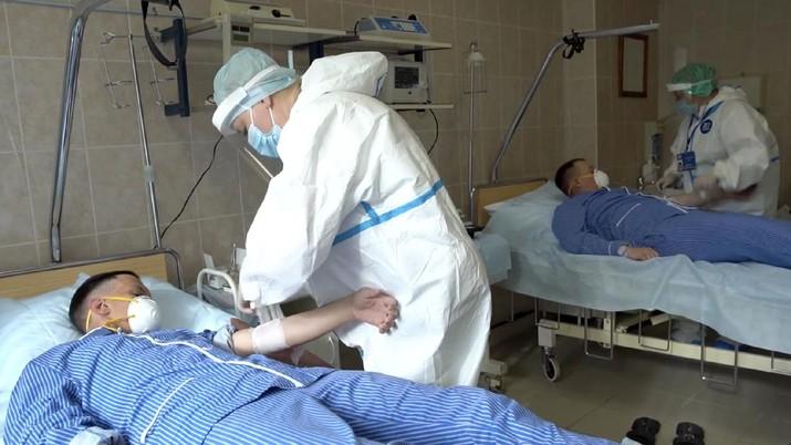 Petugas medis dengan alat pelindung mengambil darah para sukarelawan yang berpartisipasi dalam uji coba vaksin virus corona di Rumah Sakit Utama Militer Budenko di luar Moskow, Rusia.  (Russian Defense Ministry Press Service via AP)