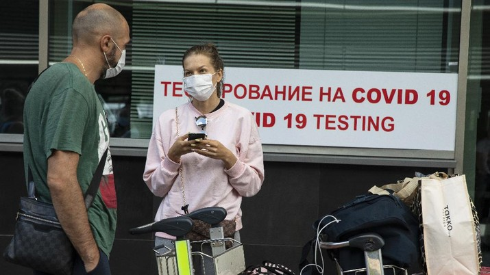 A couple queue at a COVID-19 test center at Vnukovo airport outside Moscow, Russia, Friday, Aug. 7, 2020. Authorities in Russia say they are about to approve a COVID-19 vaccine, with mass vaccinations planned as early as October 2020, using shots that are yet to complete clinical trials. But scientists worldwide are sounding the alarm that the headlong rush could backfire and point to ethical issues that undermine confidence in the Russian studies.  (AP Photo/Pavel Golovkin)