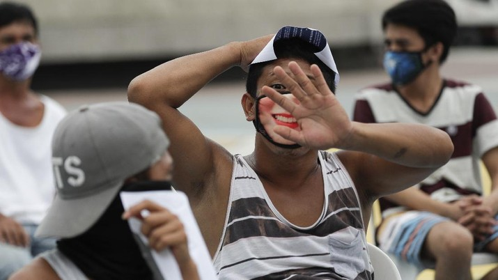 A man wearing a mask listens as they were rounded up by police at a public park for violating quarantine protocols in Quezon city, Philippines on Wednesday, Aug. 12, 2020. The residents were recorded and given lectures on community quarantine protocols before they were released as the capital and outlying provinces undergo another lockdown due to rising COVID-19 cases. (AP Photo/Aaron Favila)