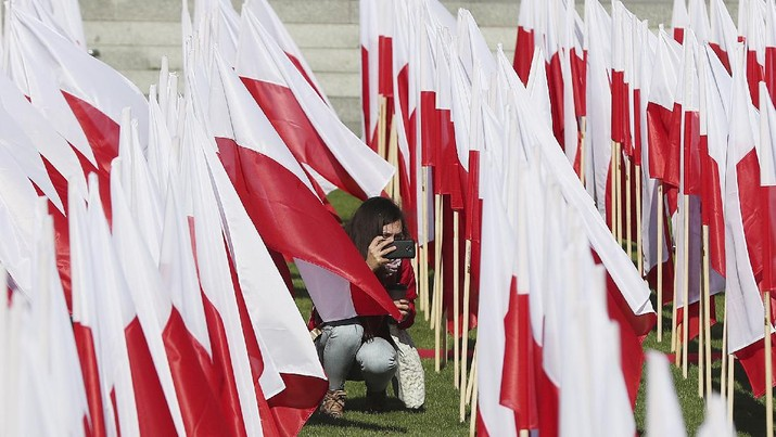 A girl takes photos of Poland's national flags arranged artistically at a popular location to mark The Day of the National Flag, in Warsaw, Poland, Saturday, May 2, 2020.(AP Photo/Czarek Sokolowski)
