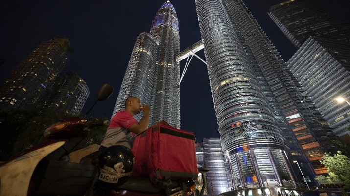 Food delivery riders break their fast in front of Twin Towers during the movement control order due to the outbreak of the coronavirus disease (COVID-19) in Kuala Lumpur, Malaysia, on Friday, May 1, 2020. Malaysia will allow most business activities to reopen from May 4, Malaysian Prime Minister Muhyiddin Yassin says the economy needs to be revived as billions have been lost during the partial lockdown that began in March. (AP Photo/Vincent Thian)