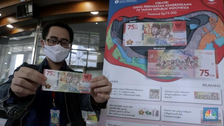 Warga menunjukkan uang baru 75.000 Ribu di Gedung BI. (CNBC Indonesia/Muhammad Sabki)