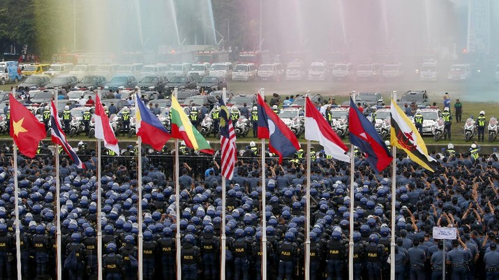 Thousands of police and soldiers watch the unveiling of the summit logo during a send off ceremony and deployment to provide security for next week's ASEAN Summit and other related summits which the country is hosting in Manila, Philippines Sunday, Nov. 5, 2017. ASEAN leaders and its Dialogue Partners such as the United States, Russia, China, Japan, South Korea, India, Turkey, Australia, Canada, New Zealand, the European Council and U.N. Secretary General Antonio Guterres are attending the summit. (AP Photo/Bullit Marquez)