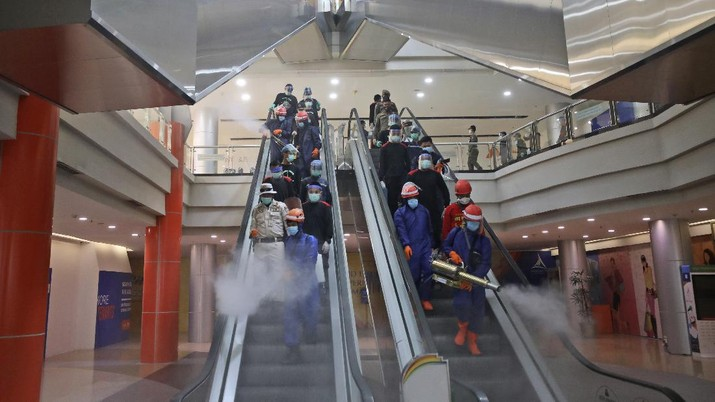 Indonesian firemen spray disinfectant to help curb the spread of the new coronavirus outbreak at Margo City shopping mall, which has been closed after a number of employees of a supermarket at the mall were tested positive for the virus, in Depok, Indonesia, Saturday, Aug. 22, 2020. (AP Photo/Dita Alangkara)