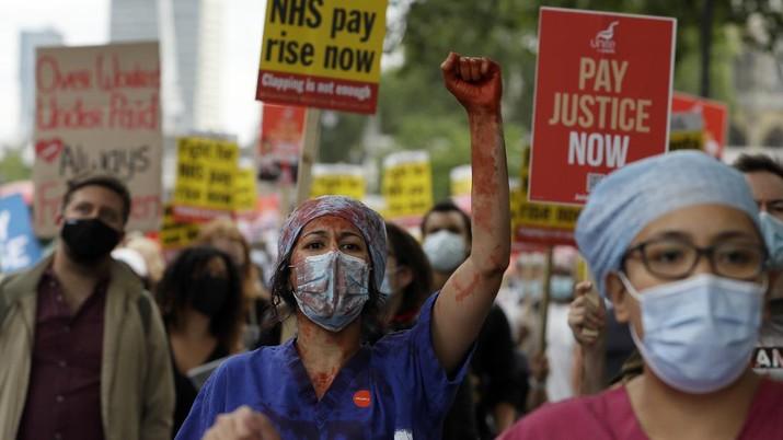 Anggota perawat dan staf Layanan Kesehatan Nasional Inggris (NHS) melakukan aksi di tengah penyebaran penyakit COVID-19, di luar Downing Street di London, Inggris. (AP/Kirsty Wigglesworth)