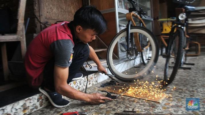 Sejumlah pekerja mengerjakan proses pembuatan sepeda kayu di Tapos, Depok, Jawa Barat. (CNBC Indonesia/Muhammad Sabki)