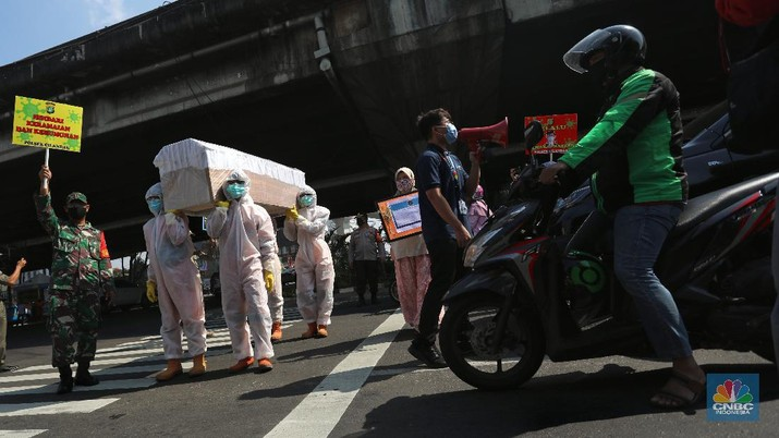 Petugas gabungan dari Kecamatan Cilandak dan Polsek Cilandak mengarak instalasi peti mati jenazah Covid-19 saat melakukan sosialisasi bahaya virus Covid-19 di kawasan Fatmawati, Jakarta. (CNBC Indonesia/Andrean Kristianto)
