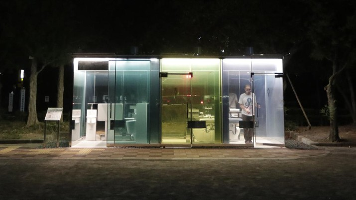 A man gets out of one of the transparent glass toilets after use at Yoyogi Hukamachi Mini Park in Tokyo on Thursday, Aug. 20, 2020. The bathrooms with the tinted wall turn opaque when it's in use. The walls of two newly installed public toilets in Tokyo's Shibuya neighborhood are see-through before people enter, but turn opaque when the doors are closed and locked from the inside. The so-called transparent toilets, which opened this month, were designed by award-winning Japanese architect Shigeru Ban for a project organized by The Nippon Foundation that redesigned a total of 17 public toilets in the neighborhood. (AP Photo/Hiro Komae)