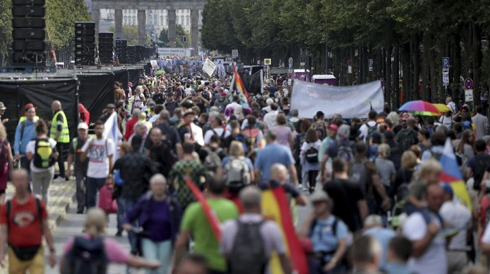 People attend a protest rally in Berlin, Germany, Saturday, Aug. 29, 2020 against new coronavirus restrictions in Germany. Police in Berlin have requested thousands of reinforcements from other parts of Germany to cope with planned protests at the weekend by people opposed to coronavirus restrictions. (AP Photo/Michael Sohn)