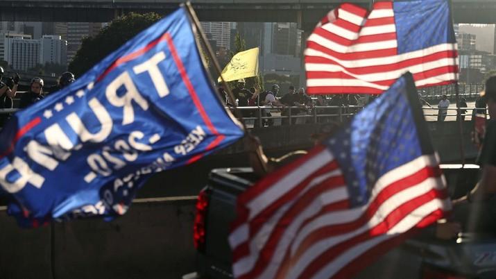 Pendukung Presiden Donald Trump menghadiri rapat umum dengan mengendari parade mobil. (AP/Dave Killen)