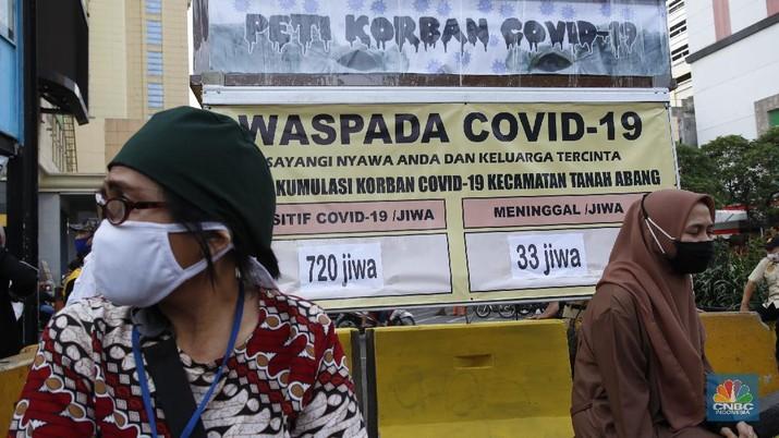 Beberapa warga sedang menunggu angkutan umum dengan latar belakang replika peti mati dan papan imbauan waspada Covid-19 di kawasan Pasar Tanah Abang, Jakarta, Selasa (1/9/2020). (CNBC Indonesia/Tri Susilo)  Instalasi replika peti mati dan papan imbauan waspada COVID-19 di sejumlah lokasi dimana DKI Jakarta masih menjadi wilayah tertinggi penyebaran. Hingga 1 September 2020 kasus terkonfirmasi COVID-19 nasional telah mencapai 177.571 kasus. Jumlah kasus positif di Jakarta 40.987, bertambah 901 per hari ini (1/9/2020).     Masih banyak warga yang kurang sadar pentingnya menggunakan masker, dan jaga jarak diruang publik.  (CNBC Indonesia/ Tri Susilo)