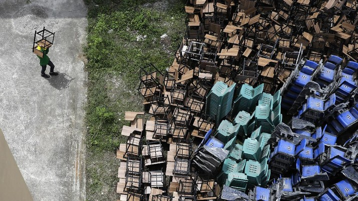 Workers carry tables as they temporarily convert a public school to a COVID-19 quarantine facility in Quezon city, Philippines, Tuesday, Sept. 1, 2020. The government continues to further ease lockdown restrictions despite the country having the most coronavirus infections in Southeast Asia. (AP Photo/Aaron Favila)