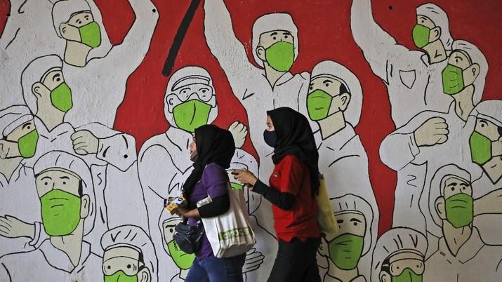 Women walk past a coronavirus-themed mural honoring health workers, in Jakarta, Indonesia, Wednesday, Aug. 26, 2020. (AP Photo/Dita Alangkara)