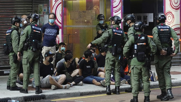 FILE - In this Wednesday, July 1, 2020, file photo, police detain a protester after being pepper sprayed during a protest in Causeway Bay before the annual handover march to mark the 23rd anniversary of Hong Kong's handover to China in 1997. Seven human rights experts affiliated with the U.N. raised concerns over Hong Kong's national security law in a letter addressed to Chinese authorities, saying that the law infringed on certain fundamental rights. (AP Photo/Vincent Yu, file)