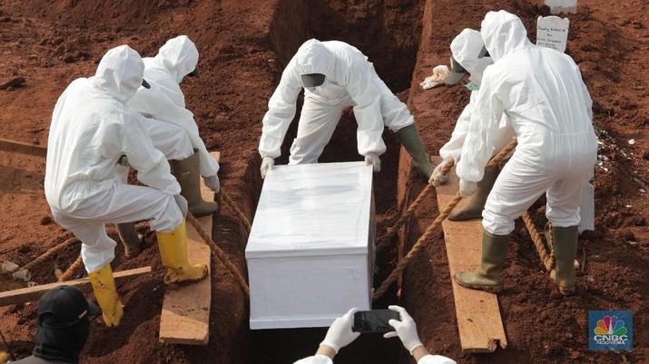 Petugas saat memakamkan pasien Covid-19 di TPU Pondok Ranggon, Jakarta Senin (7/9/2020). Petugas pemakaman mengatakan terjadi lonjakan jenazah yang terjadi dalam satu bulan lebih terakhir dengan memakamkan lebih 30 jenazah dalam satu hari. (CNBC Indonesia/Muhammad Sabki)