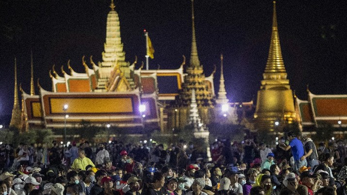 Pro-democracy demonstrators attend a protest at Sanam Luang with The Grand Palace lit up in the background in Bangkok, Thailand, Saturday, Sept. 19, 2020. Thousands of demonstrators turned out Saturday for a rally to support the student-led protest movement's demands for new elections and reform of the monarchy. (AP Photo/Sakchai Lalit)