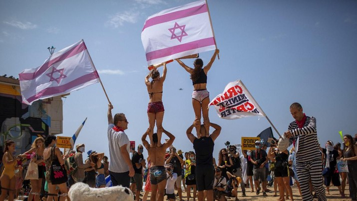 Acrobats perform as they wear face masks during a protest against government's decision to close beaches during the three-week nationwide lockdown due to the coronavirus pandemic, in Tel Aviv, Israel, Saturday, Sept 19, 2020. Israel went back into a full lockdown on Friday to try to contain a coronavirus outbreak that has steadily worsened for months as its government has been plagued by indecision and infighting. (AP Photo/Oded Balilty)