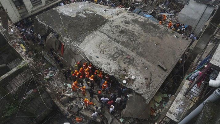 This photograph provided by India's National Disaster Response Force (NDRF) shows rescuers at the site after a residential building collapsed in Bhiwandi in Thane district, a suburb of Mumbai, India, Monday, Sept.21, 2020. (National Disaster Response Force via AP)
